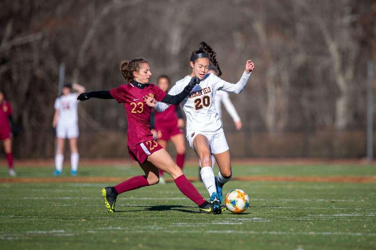 St. Joseph's Julia DiCesare (left) and Ridgefield's Julia Bragg battle for the ball during Ridgefield's 2-1 Class LL state quarterfinal win on Nov. 16, 2019.