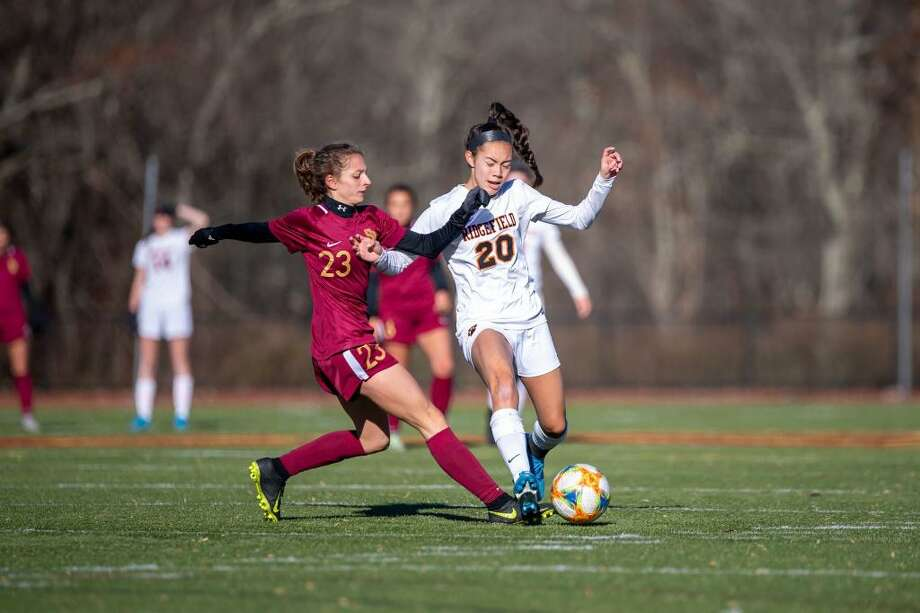 St. Joseph's Julia DiCesare (left) and Ridgefield's Julia Bragg battle for the ball during Ridgefield's 2-1 Class LL state quarterfinal win on Nov. 16, 2019. Photo: David G. Whitham / For Hearst Connecticut Media