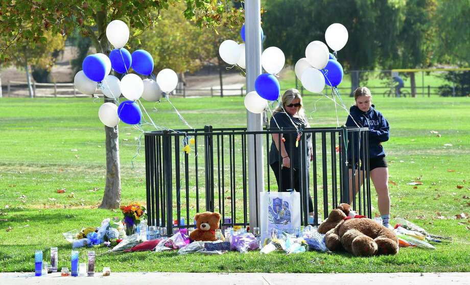 """People visit a makeshift memorial at Central Park on November 15, 2019 in Santa Clarita, California, where parents and children were reunited following the Saugus High school shooting nearby a day earlier. - A teenage boy gunned down fellow students at the school on his 16th birthday on November 14, 2019, killing two and wounding another three before turning the pistol on himself. The gunman was taken into custody in """"grave"""" condition, police said, as officers stormed Saugus High School in Santa Clarita -- the latest in a relentless cycle of classroom shootings that have left around 300 youngsters dead over two decades. (Photo by Frederic J. BROWN / AFP) (Photo by FREDERIC J. BROWN/AFP via Getty Images) Photo: FREDERIC J. BROWN / AFP or licensors"""