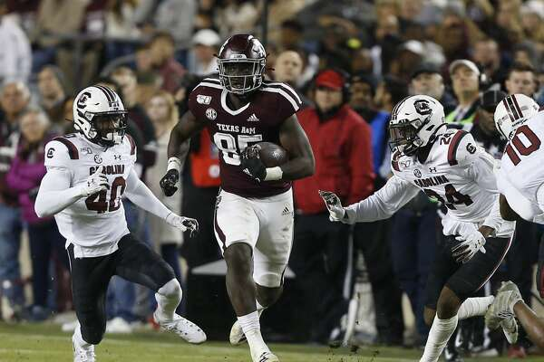 COLLEGE STATION, TEXAS - NOVEMBER 16: Jalen Wydermyer #85 of the Texas A&M Aggies runs between Jahmar Brown #40 and Israel Mukuamu #24 of the South Carolina Gamecocks after a catch during the second quarter at Kyle Field on November 16, 2019 in College Station, Texas. (Photo by Bob Levey/Getty Images)