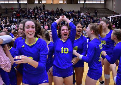 Clemens players Melinda Hackethorn, left, and Danielle Stephenson-Pino react to winning their Region IV-6A volleyball finals match versus Clark on Saturday at the Alamo Convocation Center.