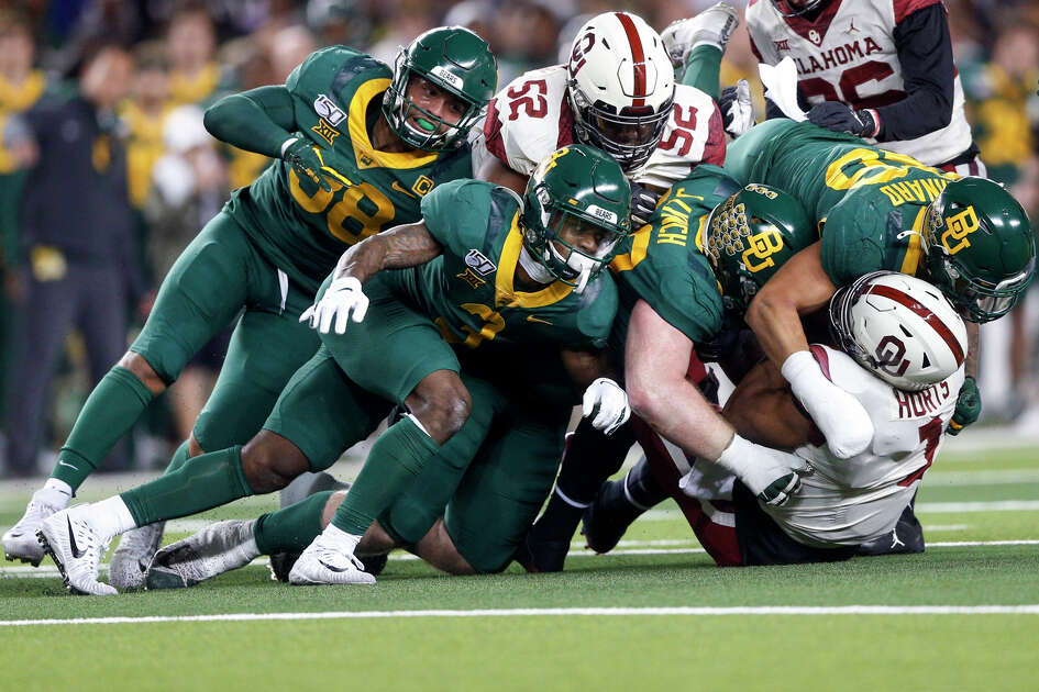 Baylor safety Chris Miller (3), defensive tackle James Lynch (93) and linebacker Terrel Bernard (26) tackle Oklahoma quarterback Jalen Hurts (1) during an NCAA college football game, in Waco, Texas, Saturday, Nov. 16, 2019. (Ian Maule/Tulsa World via AP)