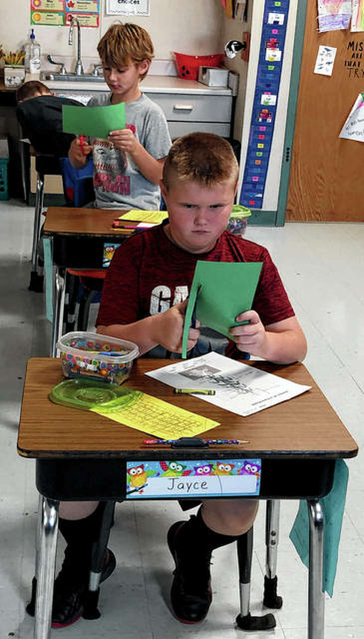Jayce Cooley (front) and Trevor Holman, students in Mrs. Havens' class, cut out templates for their corn origami crafts.