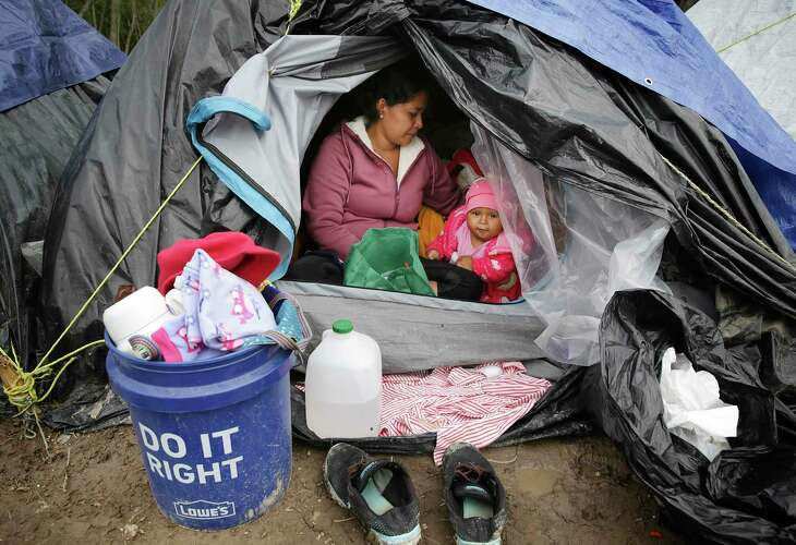 Justina Vasquez Lopez, 26, from Nicaragua, sits in her tent with her 8-month-old daughter, Samanta Vasquez.