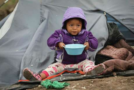 Sarai Balansar Mendez, 2-year-old from Guerrero, Mexico, eats a meal of noodles at her family's tent in the refugee camp for asylum seekers in Matamoros.