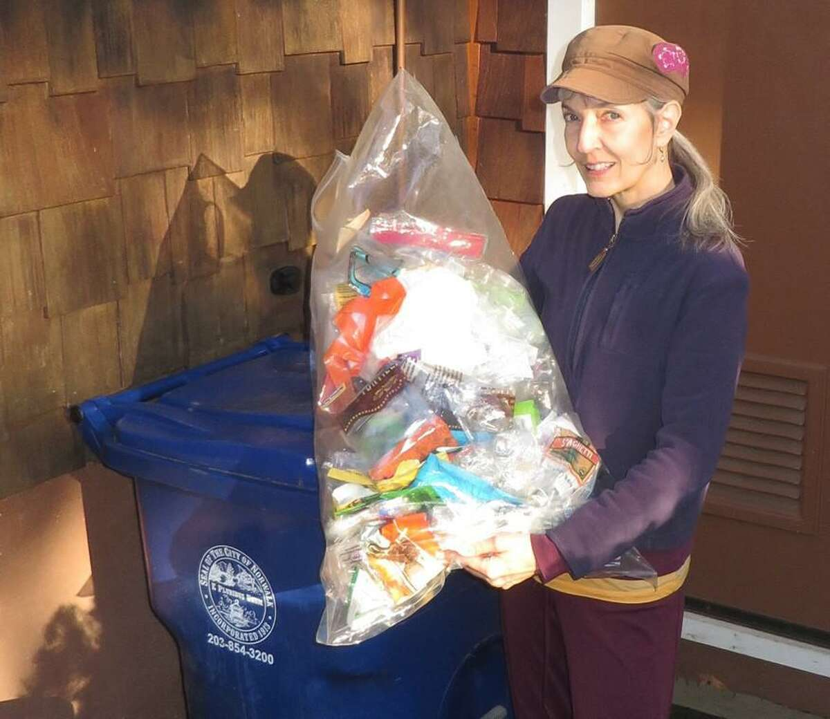Audrey Cozzarin holds a bag containing one-month's household plastic food packaging which cannot be recycled.