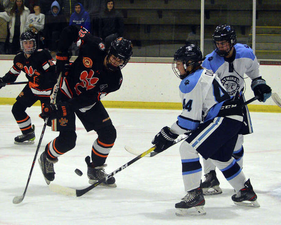Edwardsville's Will Schuster, left, goes after a loose puck during Friday's game against Westminster Christian Academy at Queeny Recreational Complex. Photo: Scott Marion/The Intelligencer