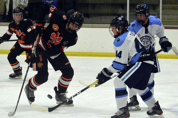 Edwardsville's Will Schuster, left, goes after a loose puck during Friday's game against Westminster Christian Academy at Queeny Recreational Complex.