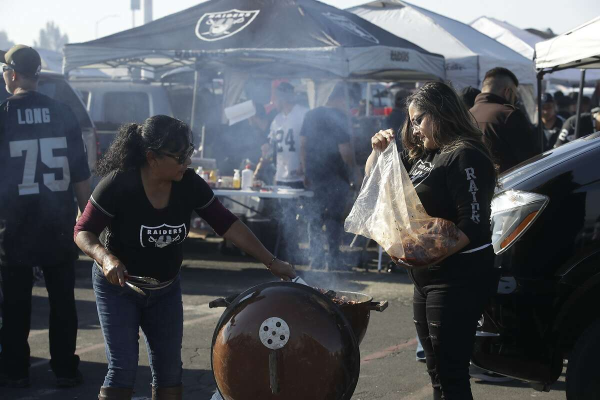 Oakland Raiders fans tailgate before the start of an NFL football game against the Cincinnati Bengals in Oakland, Calif., Sunday, Nov. 17, 2019. (AP Photo/Ben Margot)