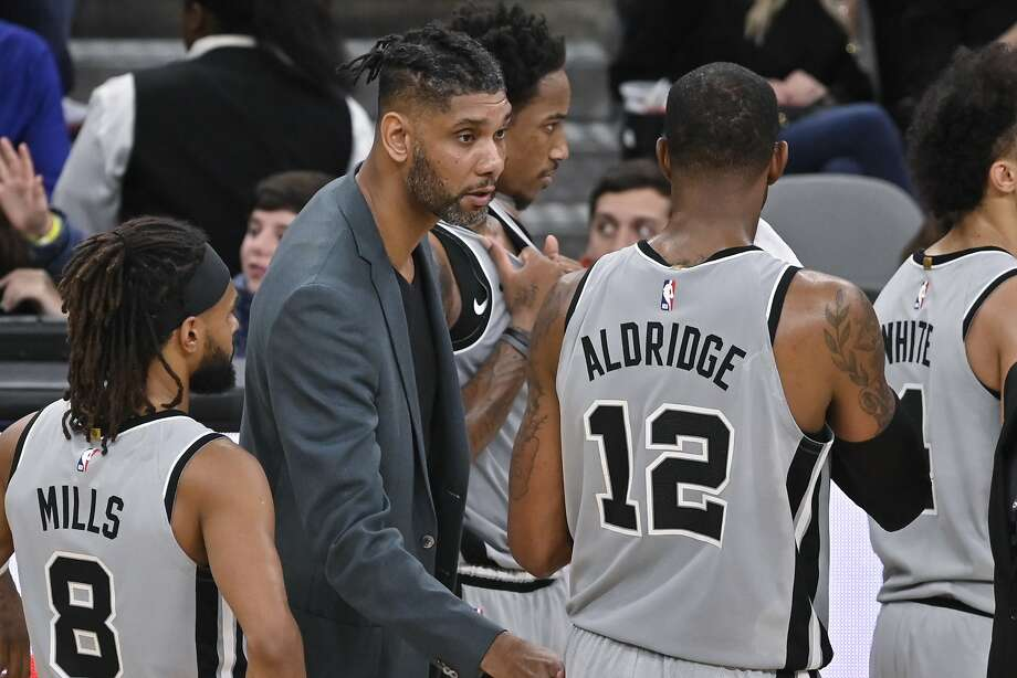 San Antonio Spurs acting head coach Tim Duncan, center, talks to Spurs forward LaMarcus Aldridge (12) as guard Patty Mills looks on during the second half of an NBA basketball game against the Portland Trail Blazers, Saturday, Nov. 16, 2019, in San Antonio. Portland won 121-116. Duncan became acting head coach after Spurs head coach Gregg Popovich was ejected after being called for two technical fouls. (AP Photo/Darren Abate) Photo: Darren Abate, Associated Press