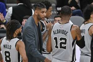 San Antonio Spurs acting head coach Tim Duncan, center, talks to Spurs forward LaMarcus Aldridge (12) as guard Patty Mills looks on during the second half of an NBA basketball game against the Portland Trail Blazers, Saturday, Nov. 16, 2019, in San Antonio. Portland won 121-116. Duncan became acting head coach after Spurs head coach Gregg Popovich was ejected after being called for two technical fouls. (AP Photo/Darren Abate)