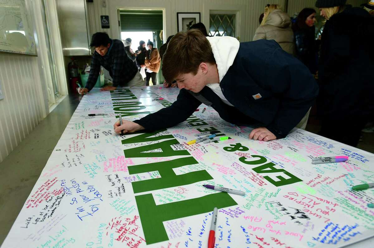 Philp Meyer signs a poster for hundreds of Greenwich teenagers and parents in helping the LIVING LIKE LUKE environmental clean up event at Greenwich Point Saturday, November 18, 2019, in Greenwich, Conn. The GHS Environmental Action Club organized the event for Luke Meyer who is environmentally conscious.