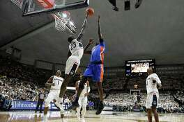 UConn's Akok Akok (23) blocks a shot by Florida's Gorjok Gak during the first half on Sunday in Storrs.