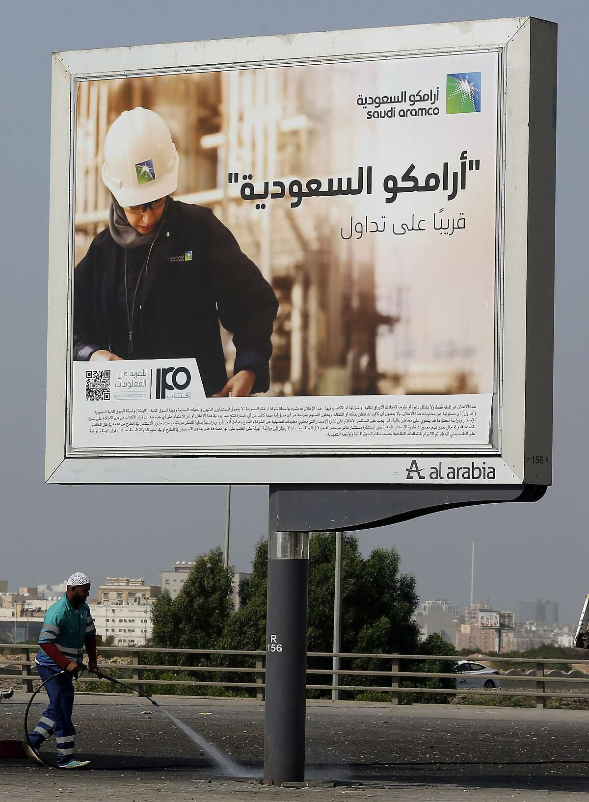 """A worker cleans under a billboard advertisement for Saudi Arabia's state-owned oil giant Aramco, with Arabic that reads, """"Saudi Aramco, soon on stock exchange,"""" in Jiddah, Saudi Arabia. (AP Photo/Amr Nabil)"""