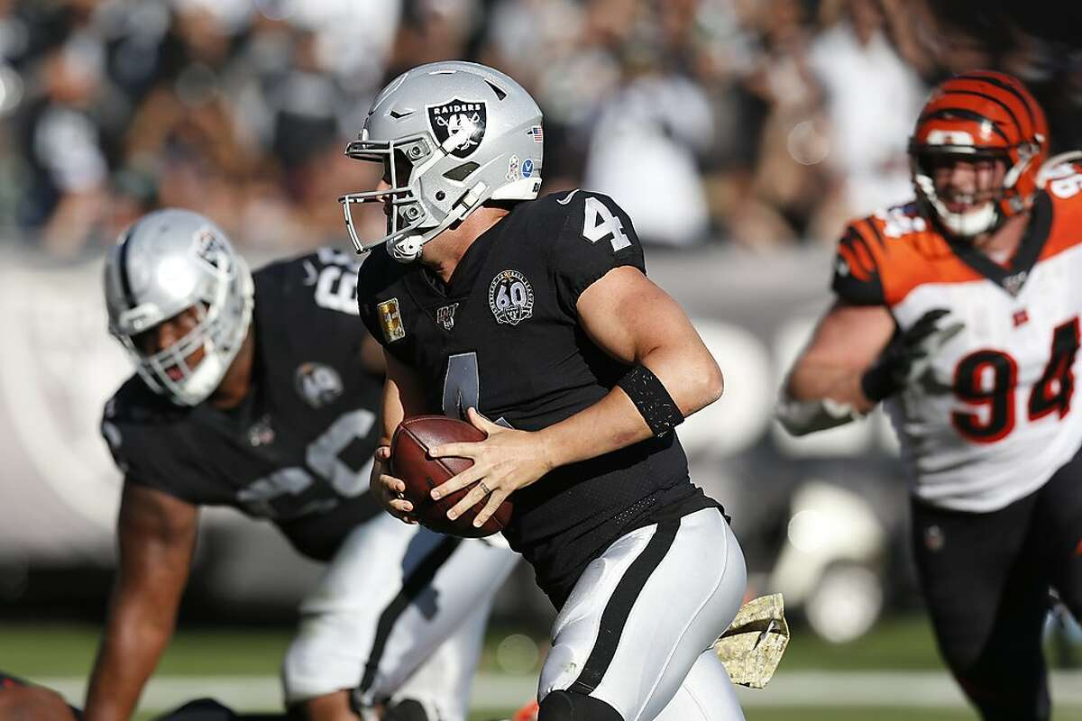Oakland Raiders quarterback Derek Carr runs with the ball for a touchdown past Cincinnati Bengals defensive end Sam Hubbard (94) during the first half of an NFL football game in Oakland, Calif., Sunday, Nov. 17, 2019. (AP Photo/D. Ross Cameron)