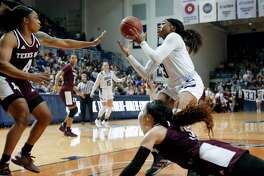 Rice guard Erica Ogwumike, top right, bobbles the ball after an attempted steal by Texas A&M guard Chennedy Carter, bottom, as Texas A&M guard Shambria Washington (4) reaches in during the second half of an NCAA college basketball game Sunday, Nov. 17, 2019, in Houston. (AP Photo/Michael Wyke)