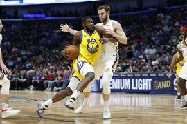 Golden State Warriors forward Eric Paschall (7) drives past New Orleans Pelicans forward Nicolo Melli in the first half of an NBA basketball game in New Orleans, Sunday, Nov. 17, 2019. (AP Photo/Tyler Kaufman)