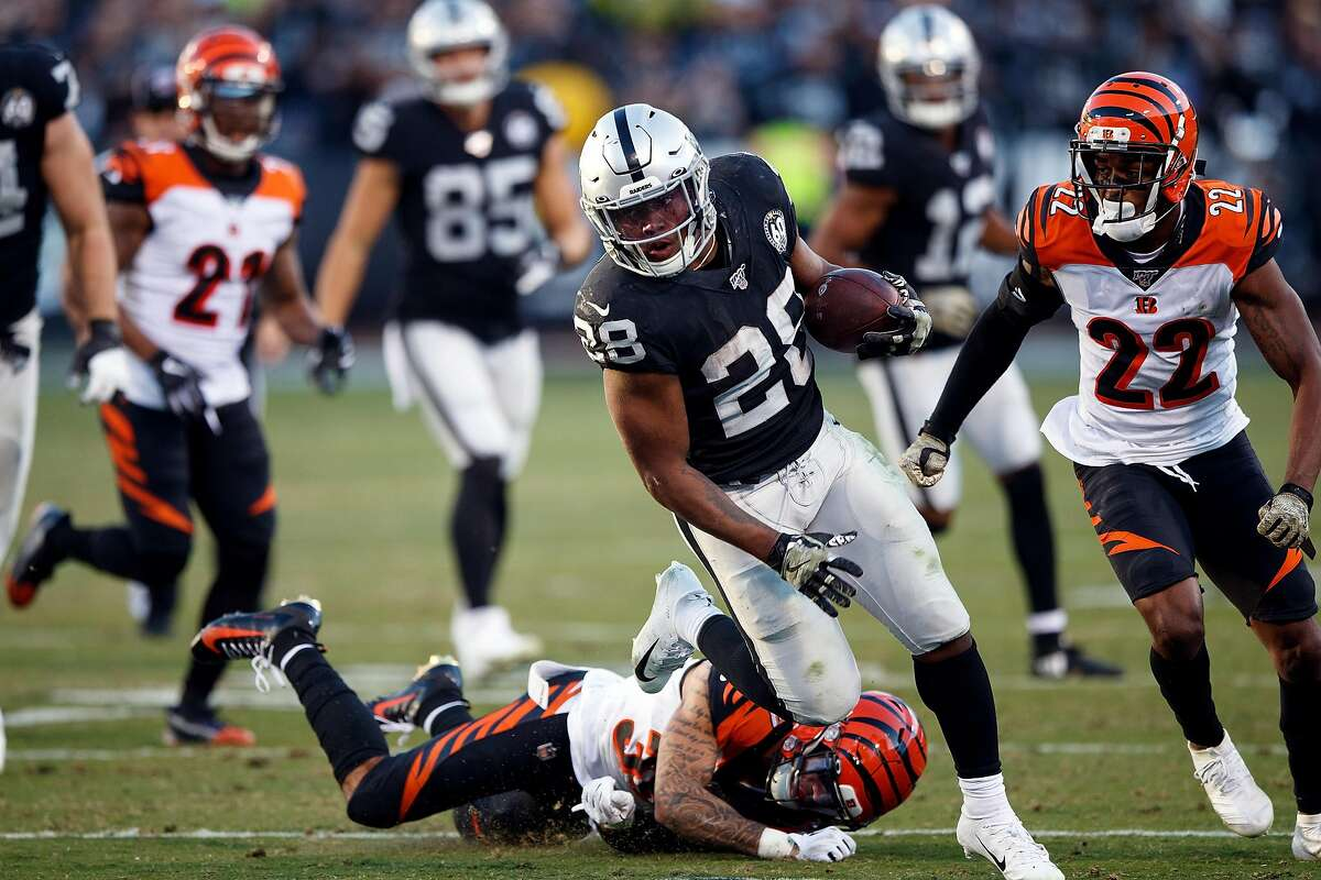 OAKLAND, CA - NOVEMBER 17: Running back Josh Jacobs #28 of the Oakland Raiders rushes past free safety Jessie Bates #30 of the Cincinnati Bengals and cornerback William Jackson #22 during the fourth quarter at RingCentral Coliseum on November 17, 2019 in Oakland, California. The Oakland Raiders defeated the Cincinnati Bengals 17-10. (Photo by Jason O. Watson/Getty Images)