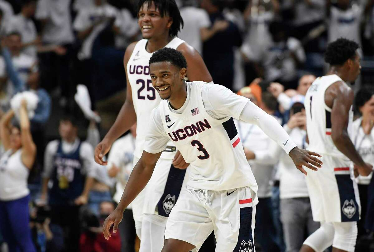 Alterique Gilbert (3) and Josh Carlton (25) celebrate at the end UConn's win over Florida in Storrs.