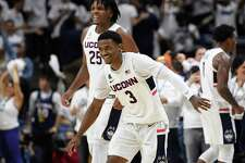 UConn's Alterique Gilbert (3) and Josh Carlton (25) celebrate at the end of Sunday's win over Florida.