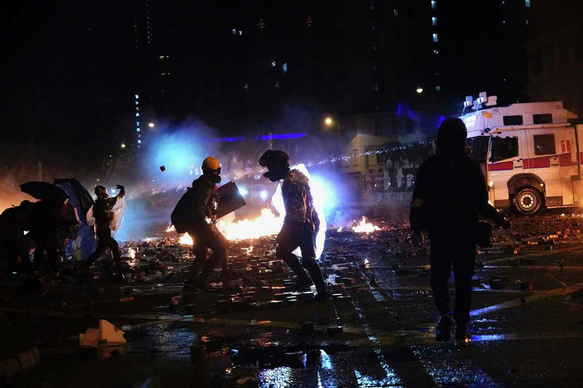 Protesters react as an armored police vehicle sprays water cannons outside of Hong Kong Polytechnic University after police gave protesters an ultimatum to leave the campus in Hong Kong, early Monday, Nov. 18, 2019. Police launched a late-night operation Sunday to try to flush about 200 protesters out of a university campus on a day of clashes in which an officer was hit in the leg with an arrow and massive barrages of tear gas and water cannons were fired. (AP Photo/Vincent Yu)