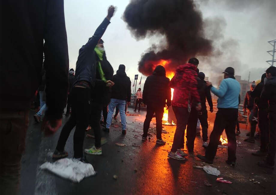 Iranian protesters gather around a fire during a demonstration against an increase in gasoline prices in the capital Tehran, on November 16, 2019. - One person was killed and others injured in protests across Iran, hours after a surprise decision to increase petrol prices by 50 percent for the first 60 litres and 300 percent for anything above that each month, and impose rationing. Authorities said the move was aimed at helping needy citizens, and expected to generate 300 trillion rials ($2.55 billion) per annum. (Photo by - / AFP) (Photo by -/AFP via Getty Images) Photo: - / AFP or licensors