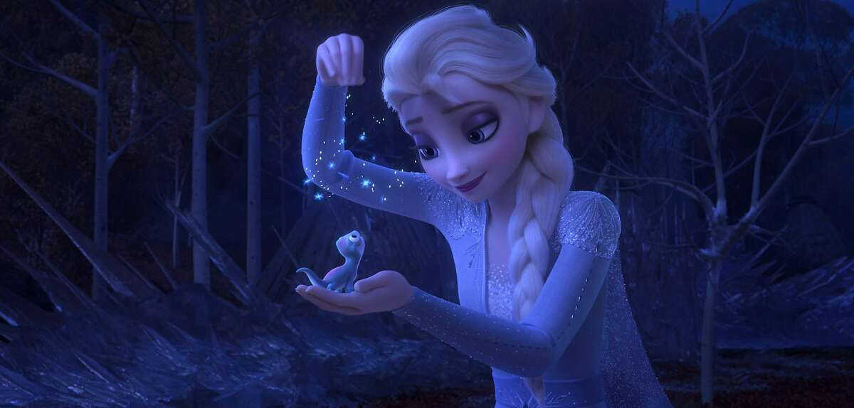 """This image released by Disney shows Elsa, voiced by Idina Menzel, sprinkling snowflakes on a salamander named Bruni in a scene from """"Frozen 2."""" (Disney via AP)"""