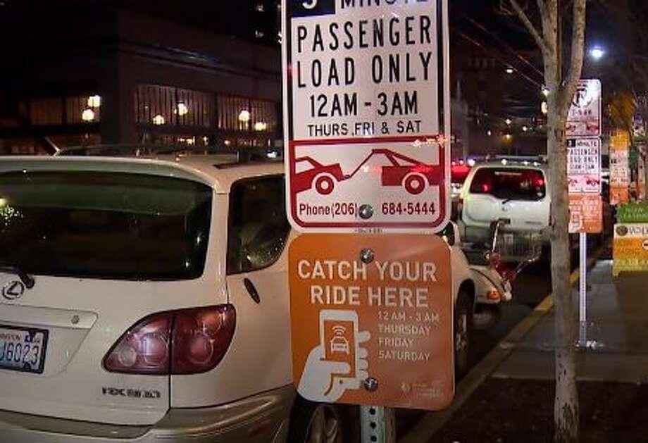 Orange signs designate pick-up zones for rideshares. Photo: Courtesy KOMO