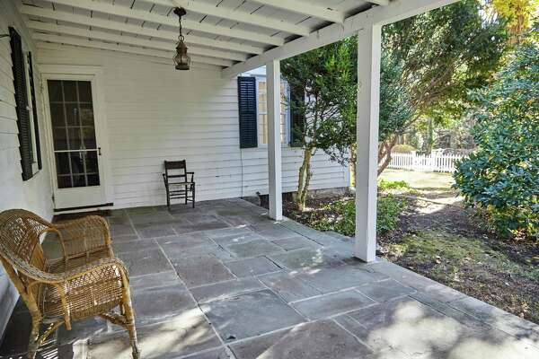 This historic house has a wide covered porch with a slate floor.