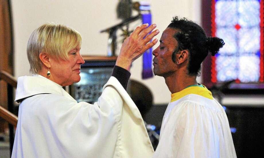 The Reverend Canon Dr. Barbara Cheney dispenses ashes to a parishioner in 2014. Photo: Hearst Connecticut Media File / Mara Lavitt