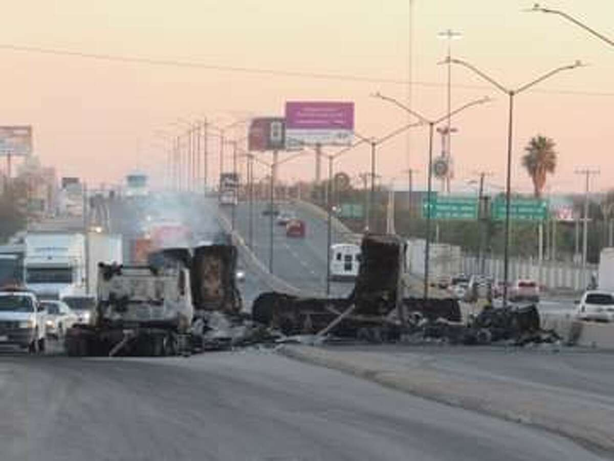 Overturned and burned vehicles are shown blocking traffic on main roads Friday in Nuevo Laredo.
