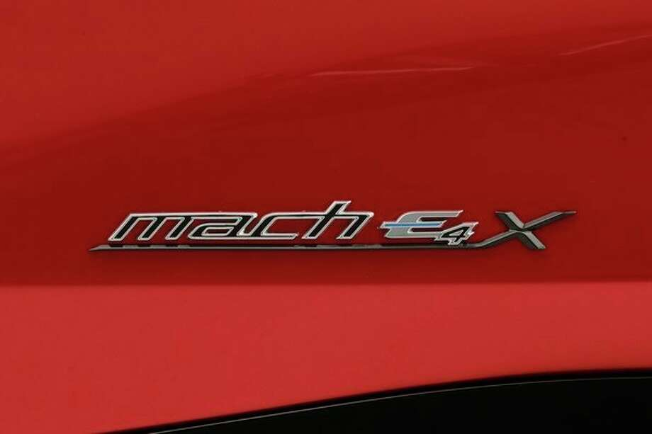 In this Wednesday, Oct. 30, 2019 photo, the name plate of the new Ford Mustang Mach-E SUV is shown in Warren, Mich. Ford is hoping to score big with the electric SUV for daily drivers that sort of looks like a Mustang performance car. The new SUV, to be unveiled just ahead of the Los Angeles Auto Show press days, should have range of up to 300 miles. It's one of dozens of electric vehicles coming globally by 2022. Automakers are eyeing what they think will be a growing market in the years to come. (AP Photo/Carlos Osorio) / Copyright 2019 The Associated Press. All rights reserved.