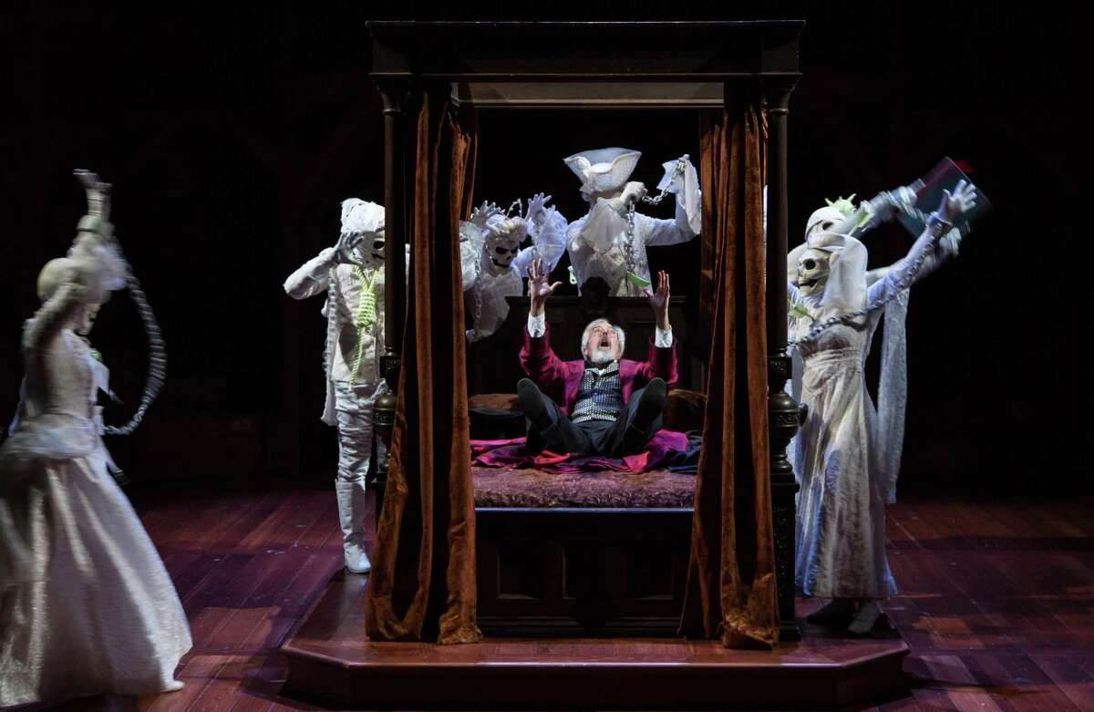 Ebenezer Scrooge is surrounded by ghosts in this scene from