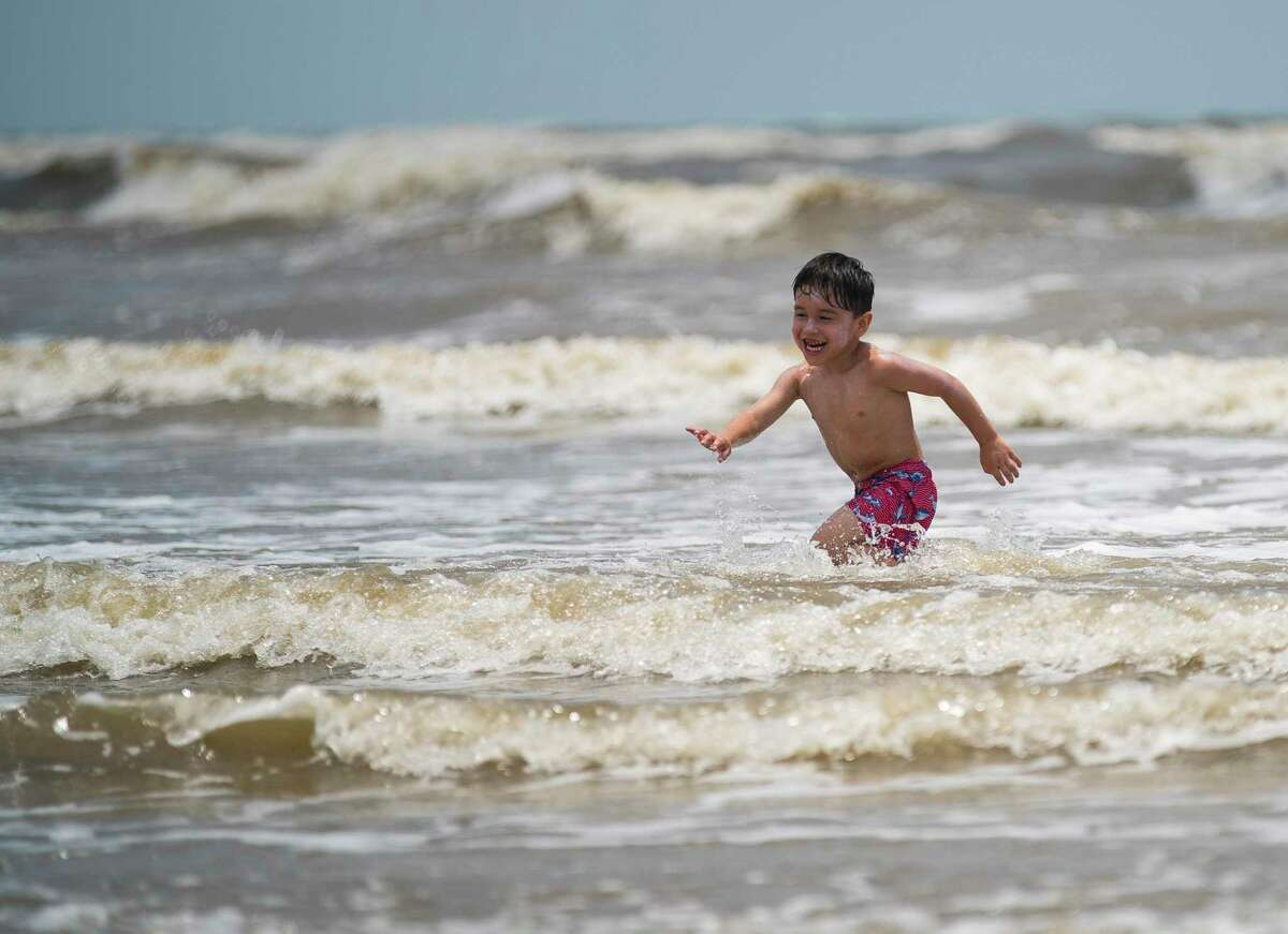 Urijah, 4, runs through the surf at the beach in Galveston while playing with his mother, Kourtney Vera.