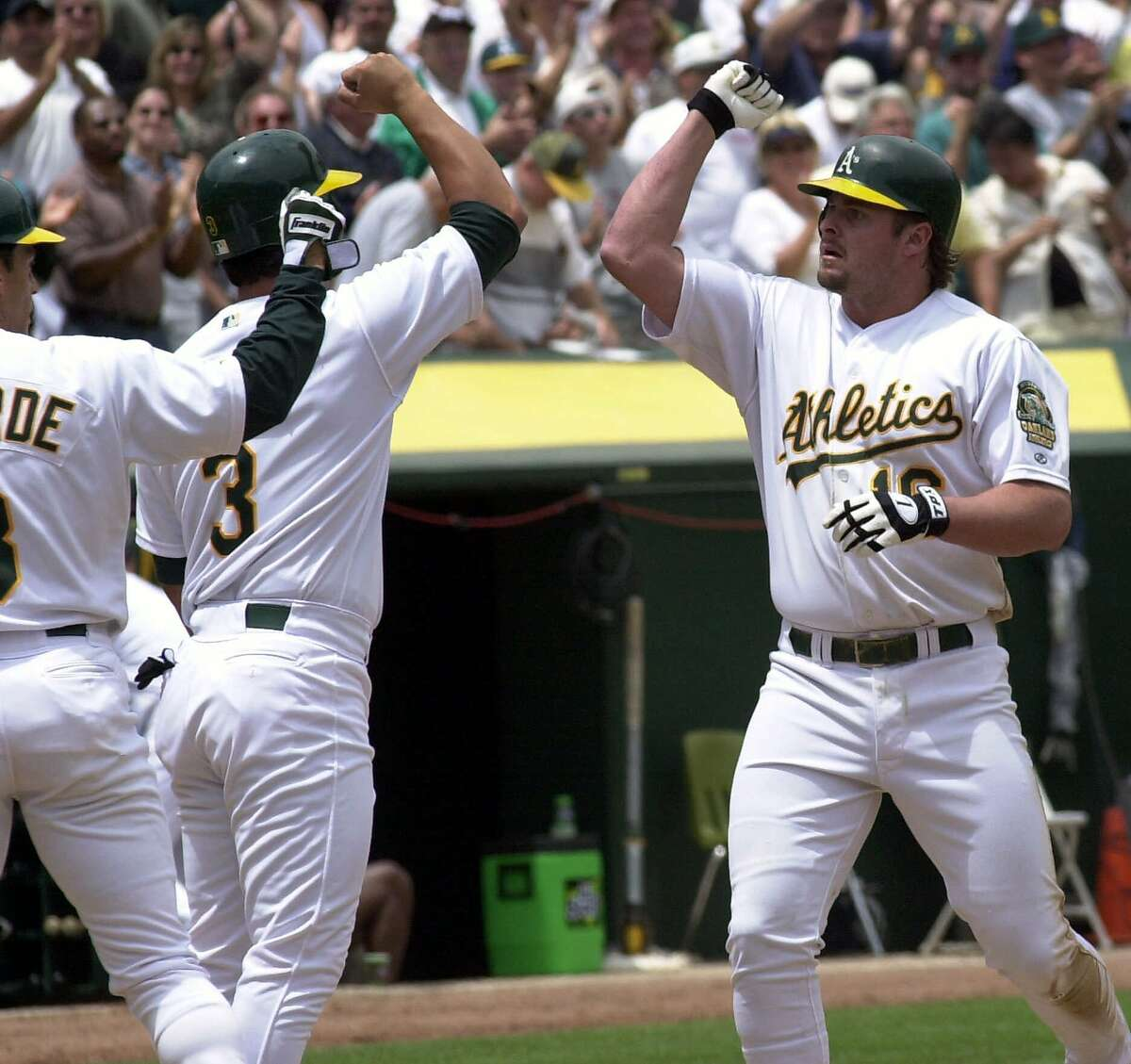 Oakland Athletics' Jason Giambi, right, is welcomed at home plate by teammates Eric Chavez (3) and Randy Velarde after hitting a grand slam off San Diego Padres' Matt Clement in the fourth inning Wednesday, June, 7, 2000, in Oakland, Calif. Chavez and Velarde both scored on Giambi's homer. (AP Photo/Susan Ragan)
