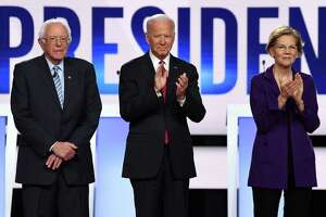 Democratic presidential hopefuls Vermont Senator Bernie Sanders, former US Vice President Joe Biden and Massachusetts Senator Elizabeth Warren arrive onstage for the fourth Democratic primary debate of the 2020 presidential campaign season Oct. 15.
