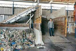 """Jack """"Tato"""" Bigio, chief executive of UBQ Materials, stands atop a pile of shredded garbage. His company will convert the trash into pellets that can be used in manufacturing plastic."""