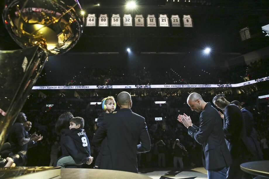 Tony Parker and his family look around as his jersey is retired while Manu Ginobili and Tim Duncan applaud on his right  as the Spurs host the Grizzlies on the night of the Tony Parker jersey retirement ceremony at the AT&T Center on Nov. 11, 2019. Photo: Tom Reel/Staff Photographer