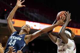 UConn guard Aubrey Griffin (44) and Temple forward Lena Niang (1) reach for a rebound during the first half Sunday in Philadelphia.