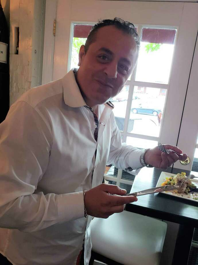 Pietro Polini tastes food inside his restaurant, TerraSole, in Ridgefield. Photo: Contributed Photo