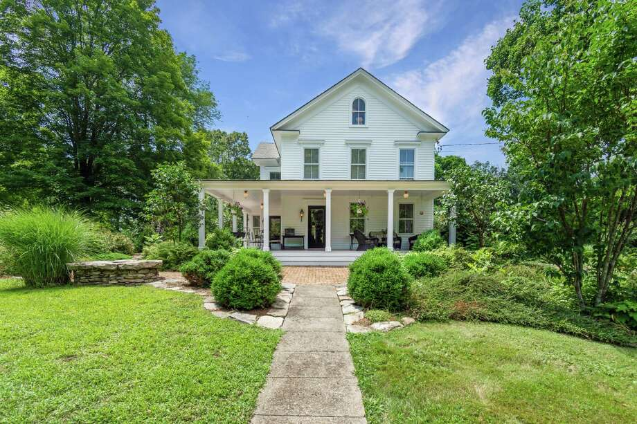 The antique colonial farmhouse, called the Messex Homestead, at 138 Old Redding Road sits on an 11.8-acre level property and features a wrap-around covered front porch.