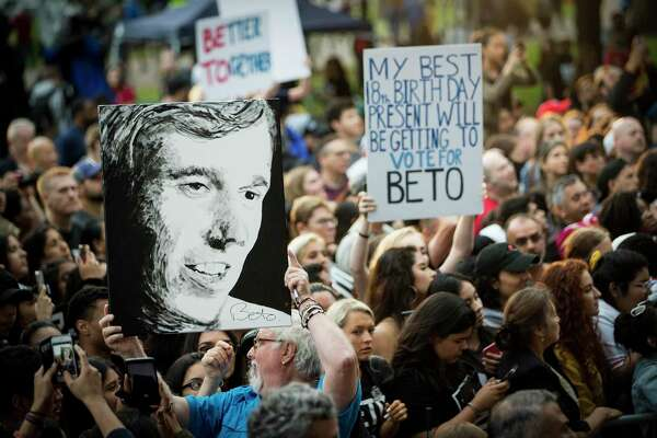 """Beto O'Rourke supporters wave signs as the presidential hopeful speaks on the campus of Texas Southern University on Saturday, March 30, 2019, in Houston. The stop in Houston is part of a 3-city """"official"""" campaign kickoff as he runs for president."""