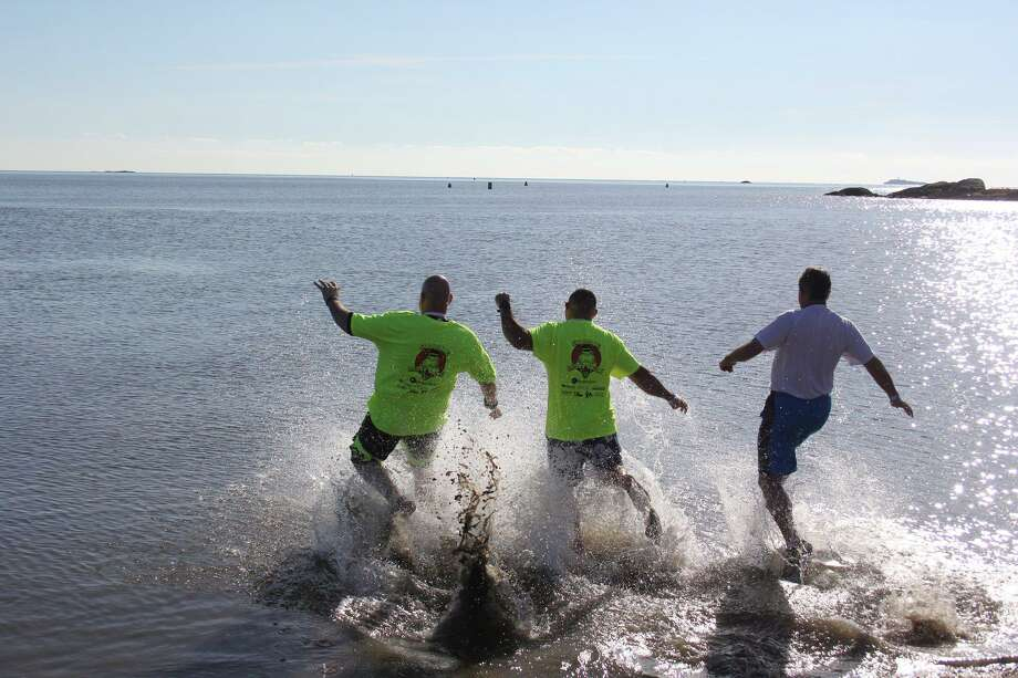 """A picture from the 2018 """"Loony Dook,"""" or penguin plunge, organized by the Guilford Police Department and held at Jacob's Beach. Participants ran into icy water in order to raise money for Special Olympics Connecticut. The second annual Loony Dook is set for Dec. 14, 2019. Photo: Guilford Police Department"""