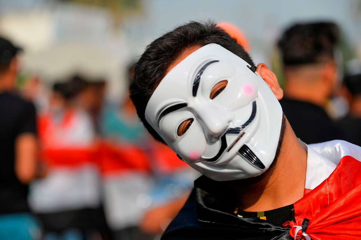 An Iraqi protester wearing a Guy Fawkes mask takes part in ongoing anti-government demonstrations in the eastern city of Diwaniyah on November 3, 2019. - Protesters in Iraq's capital and the country's south shut down streets and government offices in a new campaign of civil disobedience Sunday, escalating their month-long movement demanding change to the political system.