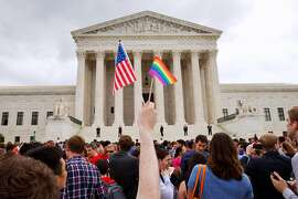 In this Friday June 26, 2015, file photo, a man holds a U.S. and a rainbow flag outside the Supreme Court in Washington after the court legalized gay marriage nationwide. After the decision, religious conservatives are focusing on preserving their right to object. Their concerns are for the thousands of faith-based charities, colleges and hospitals that want to hire, fire, serve and set policy according to their religious beliefs, notably that gay relationships are morally wrong. (AP Photo/Jacquelyn Martin)