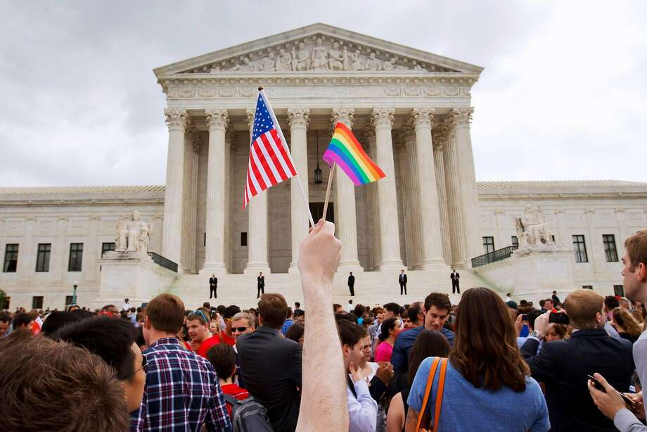 In this Friday June 26, 2015, file photo, a man holds a U.S. and a rainbow flag outside the Supreme Court in Washington after the court legalized gay marriage nationwide. After the decision, religious conservatives are focusing on preserving their right to object. Their concerns are for the thousands of faith-based charities, colleges and hospitals that want to hire, fire, serve and set policy according to their religious beliefs, notably that gay relationships are morally wrong. (AP Photo/Jacquelyn Martin) Photo: Jacquelyn Martin / Associated Press