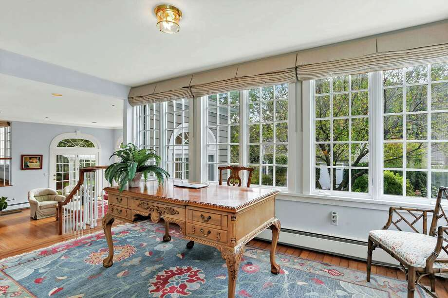 The office sits between the family room and the sunroom and features a wall of windows.