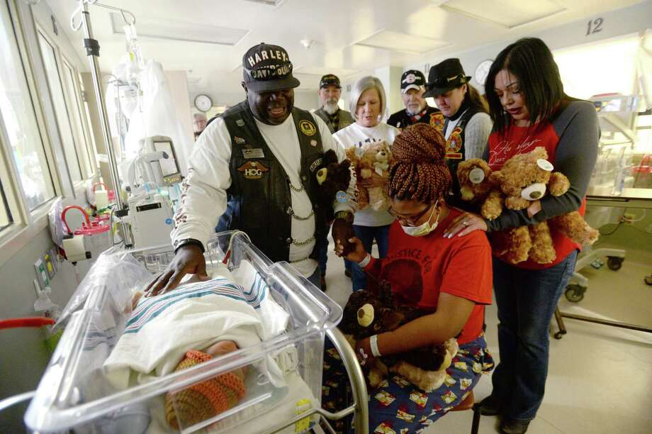 Biker and pastor Van Jordan and others gather round and pray for Tkenah Barlow and her newborn Khamdyn Cauley in the NICU unit at Baptist Hospital during the Cowboy HOG Chapter's 3rd annual Teddy Bear Run Monday. This year the group distributed 1,000 teddy bears to regional hospitals, including the Medical Center, Baptist Hospital and MD Anderson in Katy. Over 2-dozen bikers joined in Monday's event. Photo taken Monday, November 18, 2019 Kim Brent/The Enterprise Photo: Kim Brent / The Enterprise / BEN