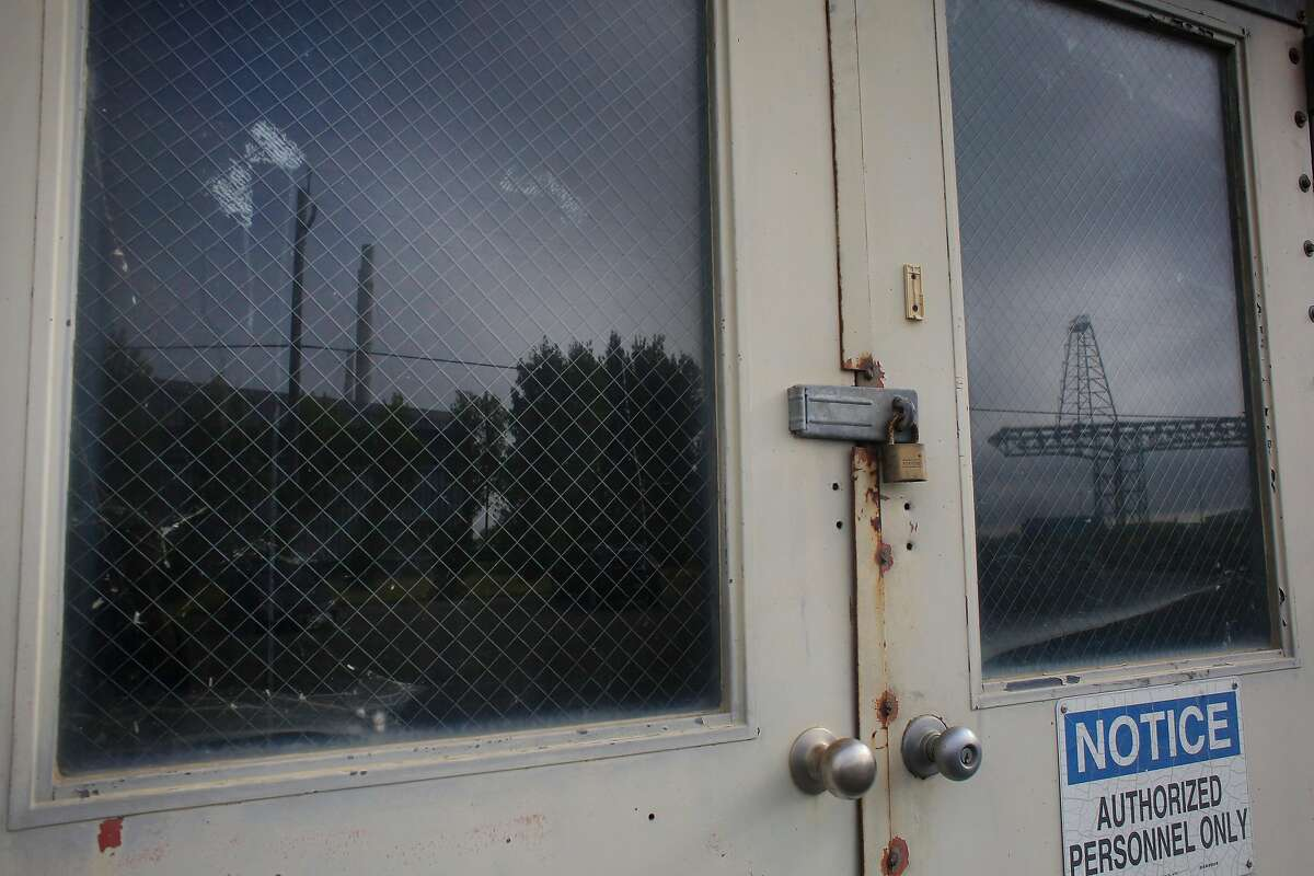 Building 606 (silhouetted in window at left) and the gantry crane (silhouetted in window at right) are reflected in the windows of a building at the former Hunters Point Naval Shipyard on Wednesday, July 25, 2018 in San Francisco, Calif.