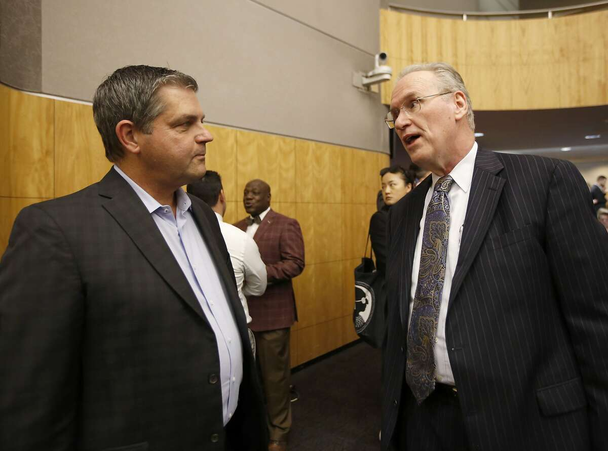 Pacific Gas & Electric CEO Bill Johnson, right, talks with Assemblyman Jim Woods, D-Santa Rosa, left, before appearing before a state Senate oversight hearing of the Energy, Utilities and Communications committee, at the Capitol in Sacramento, Calif., Monday, Nov. 18, 2019. Johnson is scheduled to testify before lawmakers about the utilities' decision to turnoff power for millions of people to prevent California wildfires. (AP Photo/Rich Pedroncelli)